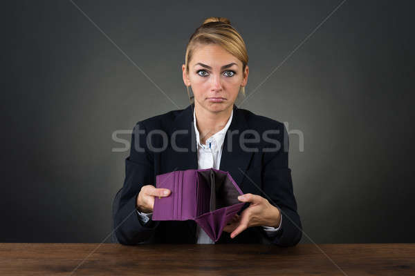 Businesswoman Showing Empty Clutch At Desk Stock photo © AndreyPopov
