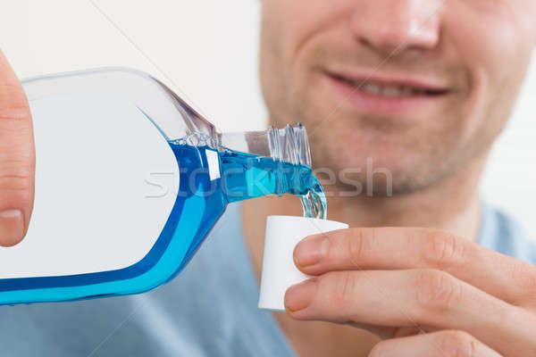 Man Pouring Bottle Of Mouthwash Into Cap Stock photo © AndreyPopov