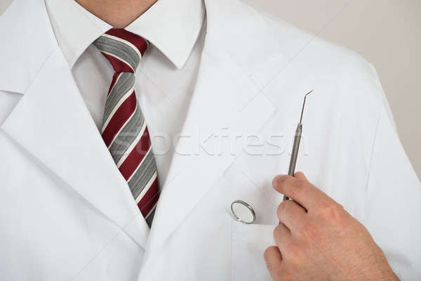 Midsection Of Dentist With Tools In Pocket Stock photo © AndreyPopov
