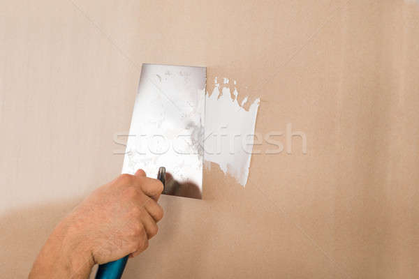 Hand Using Putty Knife On Brown Wall Stock photo © AndreyPopov