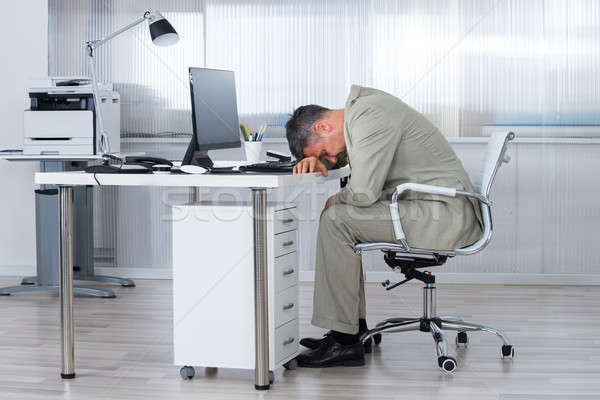 Businessman Sleeping On Desk In Office Stock photo © AndreyPopov
