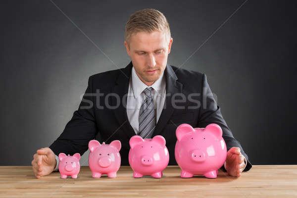 Businessman With Piggybanks On Wooden Desk Stock photo © AndreyPopov