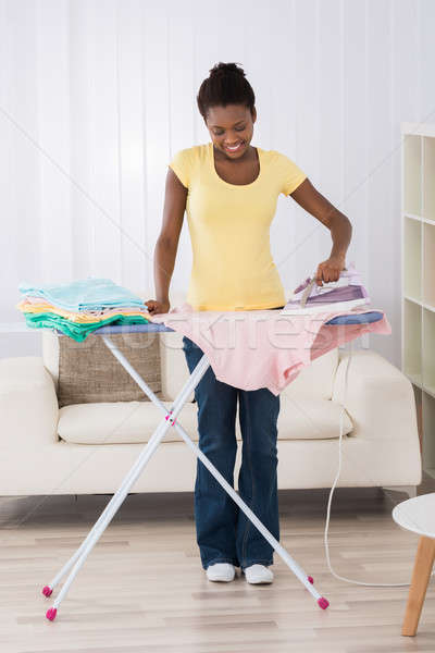 Happy Woman Ironing Clothes On Iron Board Stock photo © AndreyPopov