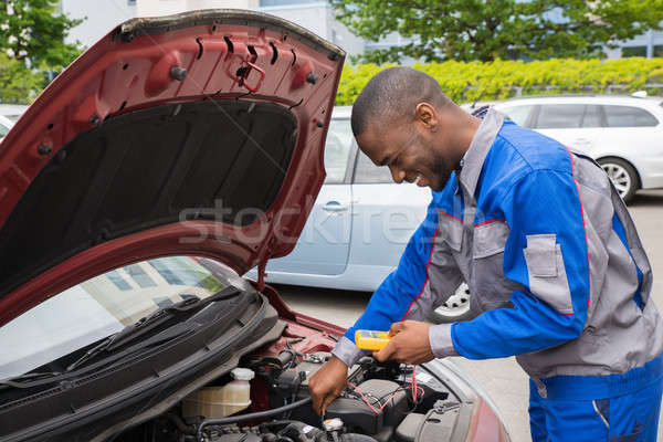 Mechanic Using Multimeter To Check Car Battery Stock photo © AndreyPopov