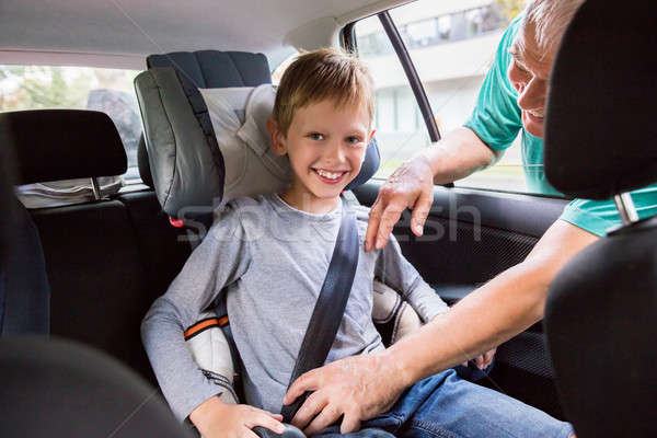 Grandfather Buckling Up On Grandson In Car Safety Seat Stock photo © AndreyPopov