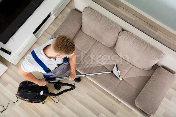 Fiatalember takarító kanapé porszívó magasról fotózva kilátás Stock fotó © AndreyPopov