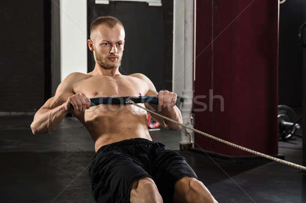 Young Man Using Rowing Machine Stock photo © AndreyPopov