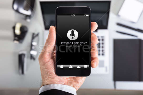 Text On Smart Phone Screen Held By Businessman In Office Stock photo © AndreyPopov