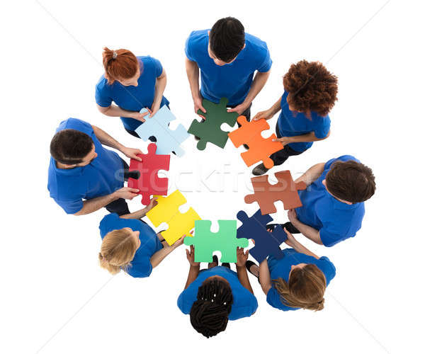 High Angle View Of Multiracial Janitors Solving Jigsaw Puzzle Stock photo © AndreyPopov