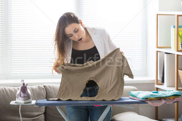 Woman Looking At Burnt T-shirt At Home Stock photo © AndreyPopov