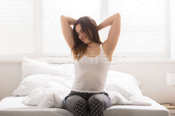 Happy Sleepy Woman On Bed Stock photo © AndreyPopov