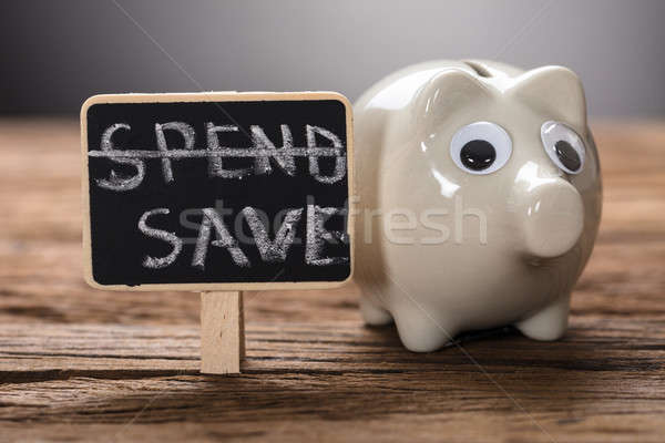 Closeup Of Piggybank By Spend Save Sign On Wood Stock photo © AndreyPopov