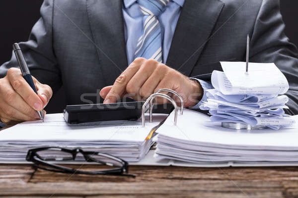 Businessman Calculating Invoice With Bill Stand On Documents Stock photo © AndreyPopov
