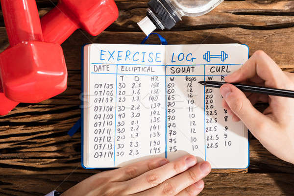 Elevated View Of A Hand Filling Exercise Log On Notebook Stock photo © AndreyPopov