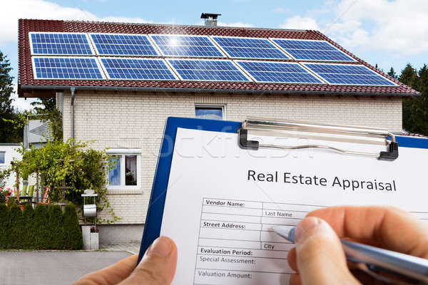 Stock photo: Hand Filling Real Estate Appraisal Form In Front Of House