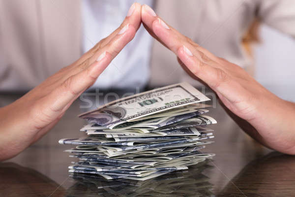 Businesswoman Hand Protecting Stack Of Hundred Dollar Bills Stock photo © AndreyPopov