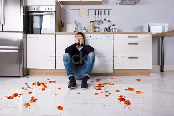 Man Sitting On Kitchen Floor With Spilled Food Stock photo © AndreyPopov