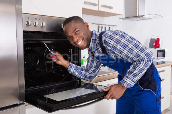 Repairman Fixing Kitchen Oven Stock photo © AndreyPopov