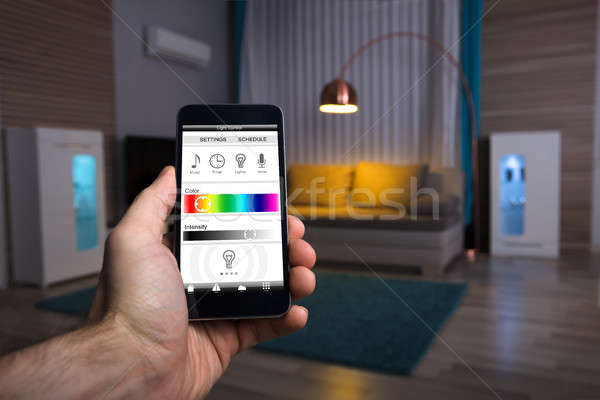 Human Hand Adjusting Electric Light Through Mobile Phone Stock photo © AndreyPopov