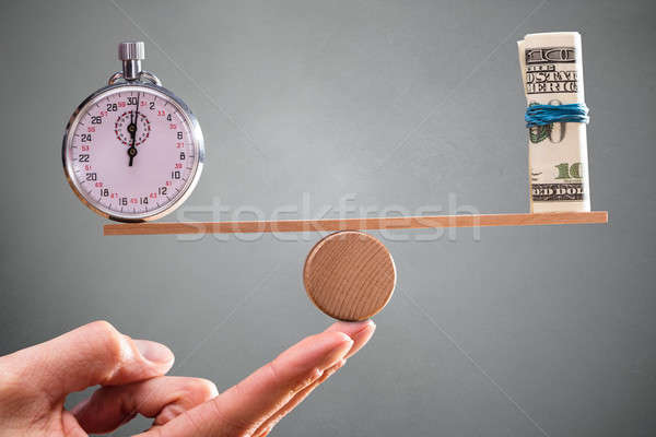 Hand With Balance Between Stopwatch And Rolled Up Banknotes Stock photo © AndreyPopov