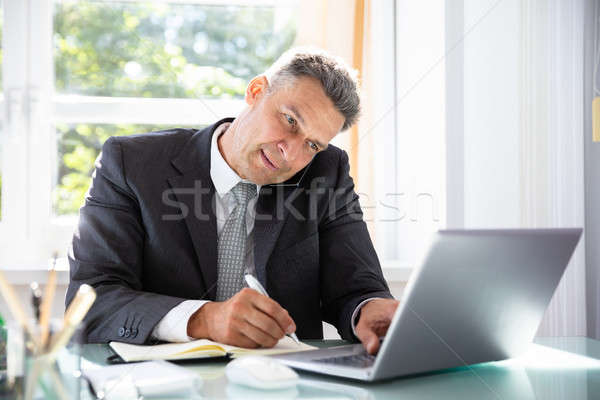 Businessman Talking On Cellphone While Writing Schedule In Diary Stock photo © AndreyPopov
