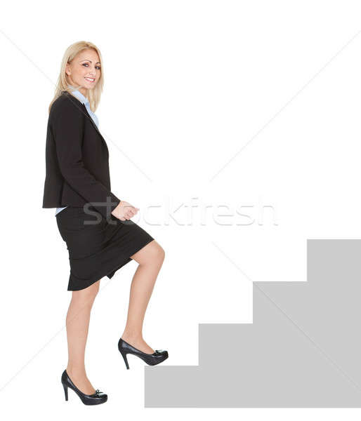 Successful businesswoman walking up a staircase Stock photo © AndreyPopov