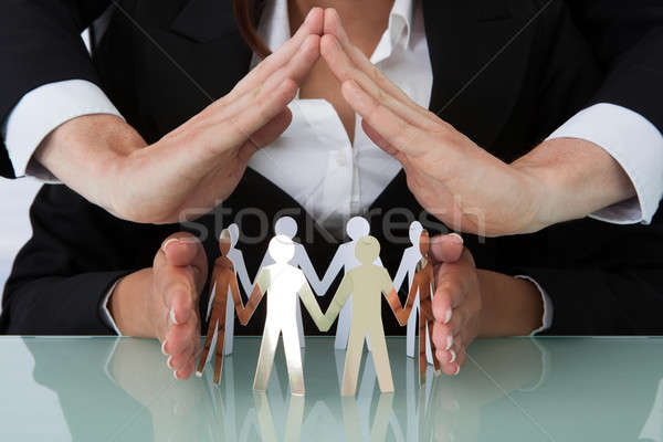 Business People Sheltering Team Of Paper People At Desk Stock photo © AndreyPopov