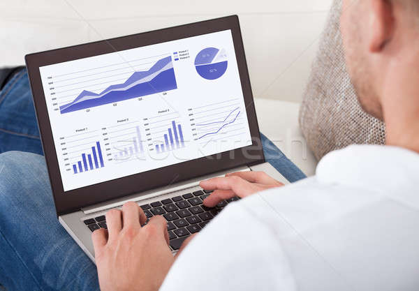 Businessman analyzing graphs on his laptop Stock photo © AndreyPopov