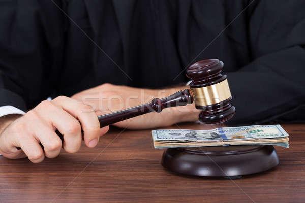 Judge Striking Gavel On Banknotes At Desk Stock photo © AndreyPopov
