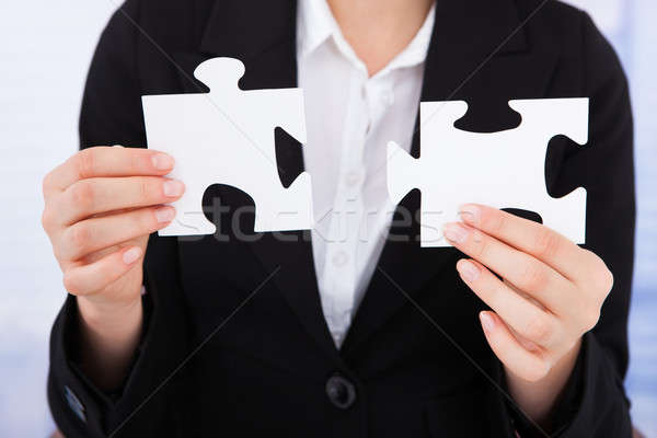 Businesswoman Joining Jigsaw Pieces Stock photo © AndreyPopov