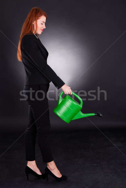 Businesswoman Using Green Watering Can Stock photo © AndreyPopov