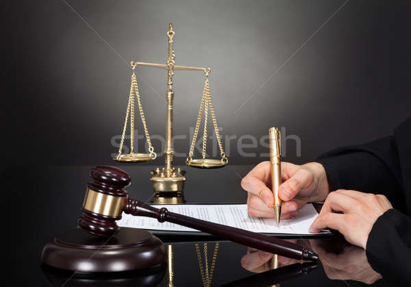 Male Judge Signing Document At Desk Stock photo © AndreyPopov