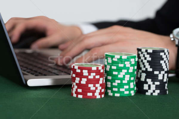 Businessman Using Laptop By Stacked Casino Chips Stock photo © AndreyPopov