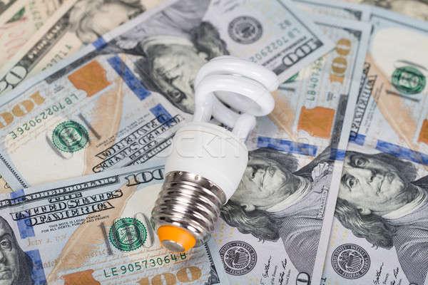 Energy Saving Bulb On Dollar Bills Stock photo © AndreyPopov