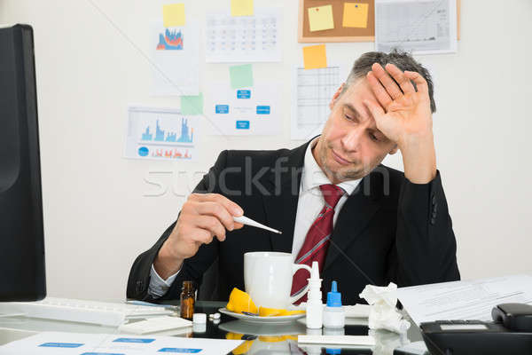 Businessman Looking At Thermometer Stock photo © AndreyPopov