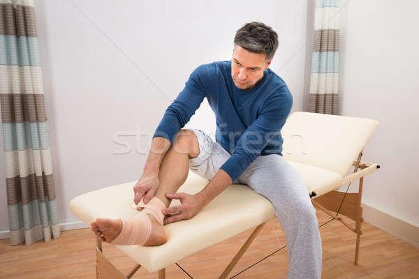 Férfi bandázs láb ül ágy gépel Stock fotó © AndreyPopov