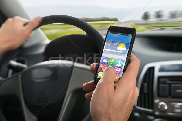 Person's Hand Using Cellphone While Driving A Car Stock photo © AndreyPopov