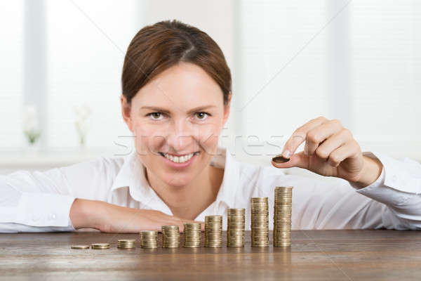 Stock photo: Businesswoman Placing Coin To Stack Of Coins
