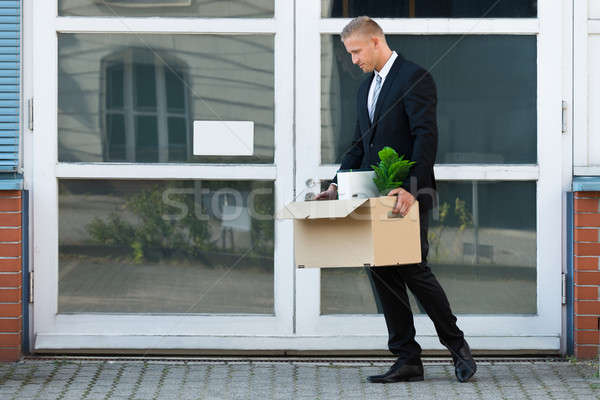 Businessman Carrying His Belongings In Box After Being Fired Stock photo © AndreyPopov