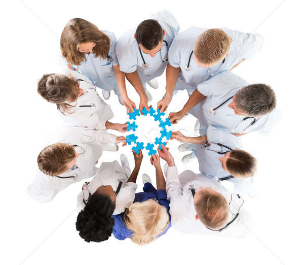Medical Team Joining Jigsaw Pieces While Standing In Huddle Stock photo © AndreyPopov