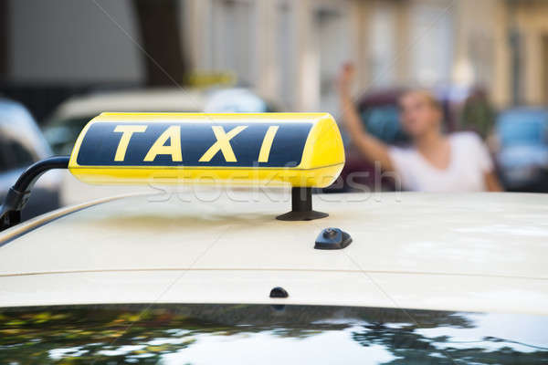 Woman Raising Arm To Hail Taxi On Street Stock photo © AndreyPopov