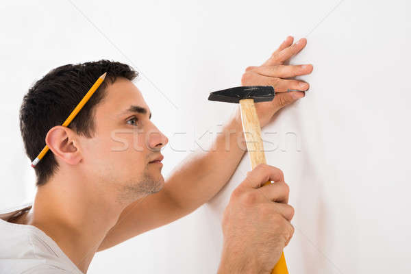 Man Hammering Nail On White Wall Stock photo © AndreyPopov