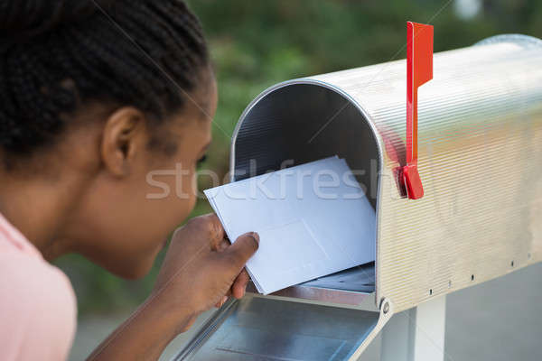 Woman Putting Letter In Mailbox Stock photo © AndreyPopov