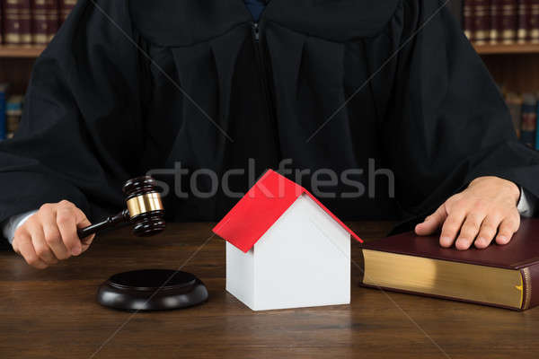 Judge With House Model Hitting Gavel At Desk Stock photo © AndreyPopov