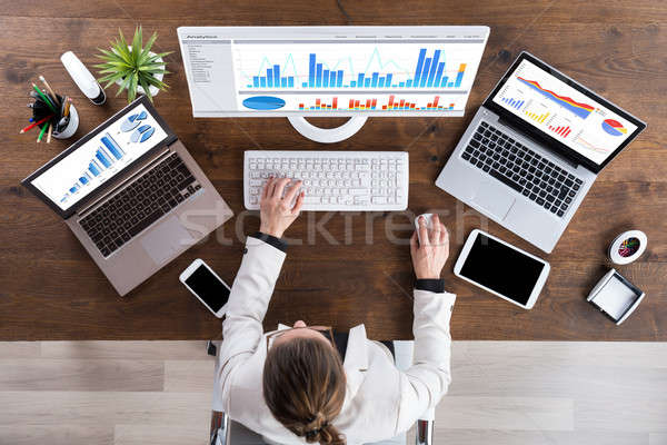 Businesswoman Working With Graphs On Computer Stock photo © AndreyPopov