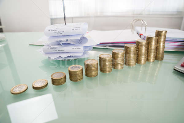 Stack Of Coins With Paper Nail On Desk Stock photo © AndreyPopov