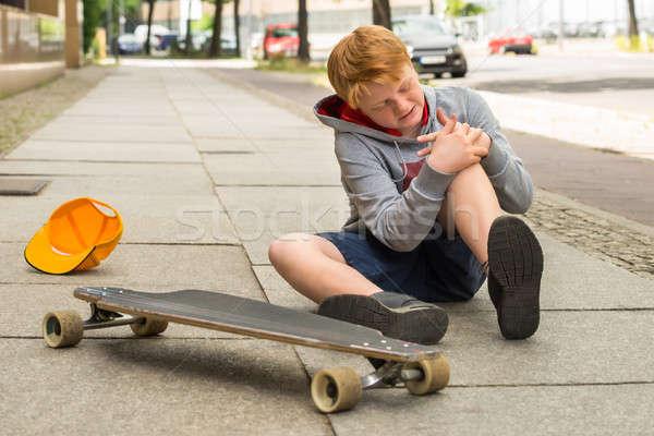Nino mirando herido pierna sesión skateboard Foto stock © AndreyPopov