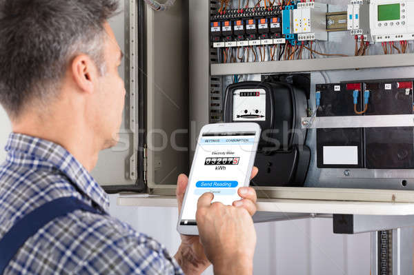 Technician Doing Meter Reading Using Mobilephone Stock photo © AndreyPopov