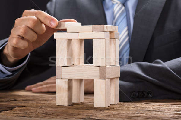 Businessman Building Tower With Wooden Blocks Stock photo © AndreyPopov