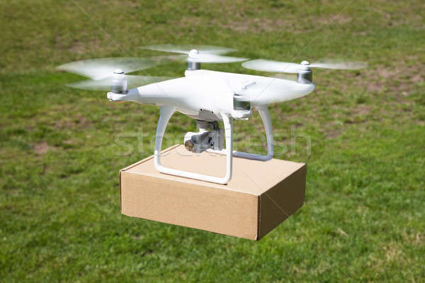 Drone carrying parcel over grassy field Stock photo © AndreyPopov